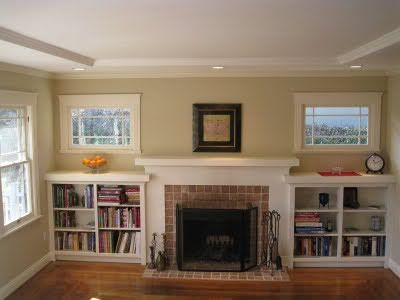 Bookcases around shallow fireplace.