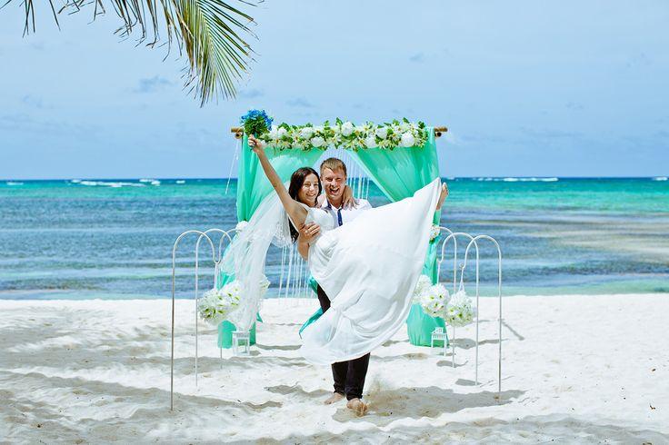 Символическая церемония на пляже. Бирюзовая свадебная арка. Муж несёт невесту на руках