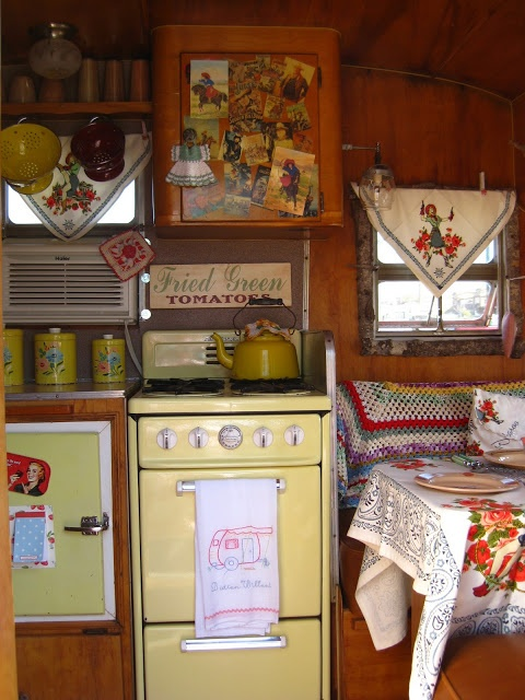 Cute camper interior. Wood, pastels, embroidered bunting, granny blankets, and table cloths