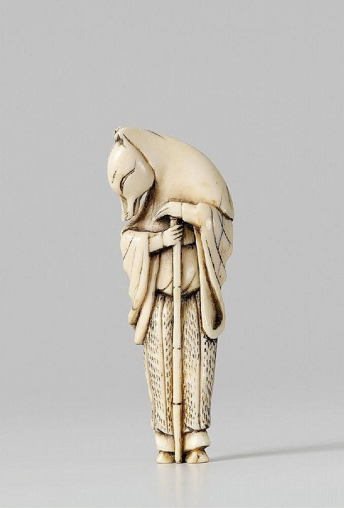 An ivory netsuke of Hakusôzu. Early 19th century. 	The sly fox who has changed into a priest, the head turned sideways and covered by a hood, both his human hands placed on the bamboo cane.