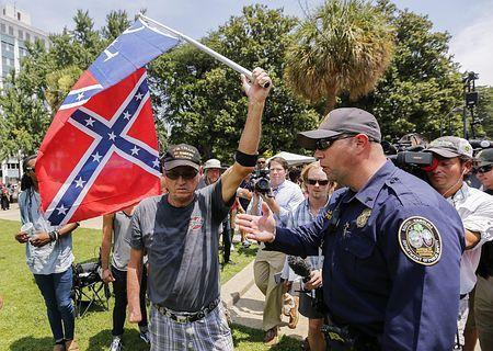 18日、米南部サウスカロライナ州の州都コロンビアの州議会議事堂前で、南軍旗を振りかざす男性(EPA=時事) ▼19Jul2015時事通信|南軍旗撤去に抗議=白人至上団体-米サウスカロライナ州 http://www.jiji.com/jc/zc?k=201507/2015071900064