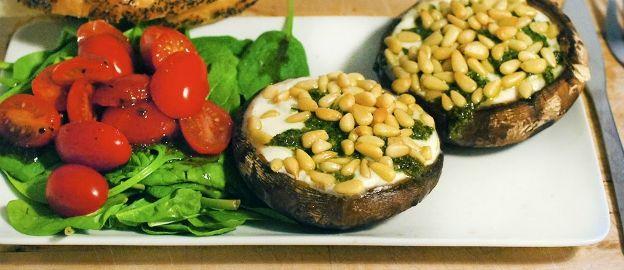 Portobello met mozzarella, pesto en pijnboompitjes en spinaziesalade