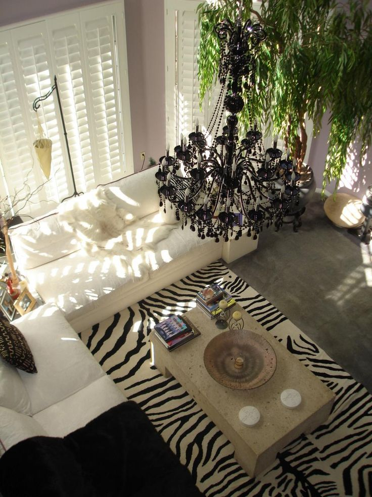 This eclectic living room with high ceilings and a large black beaded chandelier features a zebra print area rug, concrete coffee table, window shutters and white sofas.