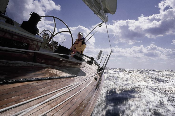 Skipper at helm of yacht low angle view with spray of the sea and dramatic clouds.