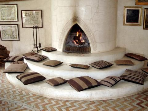 Sculpted tadelakt fireplace and soft seating set against zigzagging bijmat and glazed tiling from Palais Rhoul in Marrakech