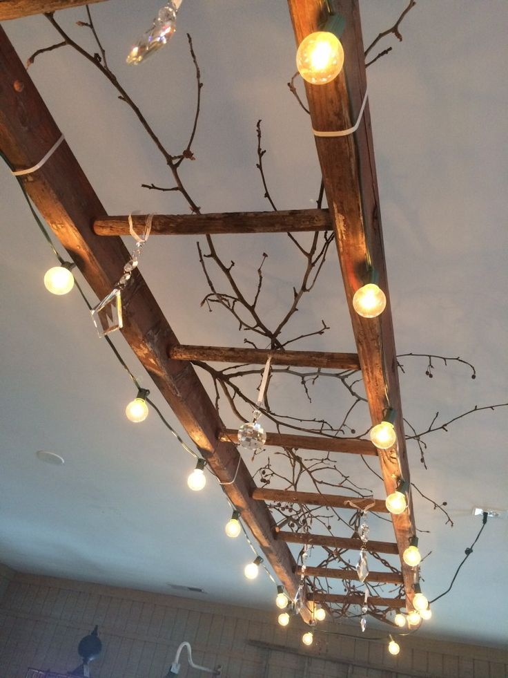 A vintage wooden ladder makes great lighting. This one is wrapped with globe lights, and decorated with vintage chandelier crystals and branches.