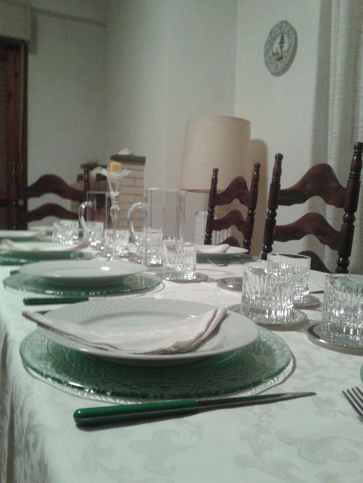 Tovaglia bianca di fiandra, sottopiatti in cristallo, piatti in porcellana bianca, posate in acciaio con manico verde, bicchieri tumbler di cristallo con sottobicchieri in argento. Centrotavola: piccolo candelabro in cristallo con candela gialla.