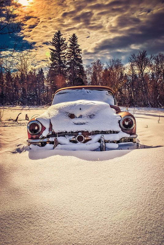 Old car rusting in the snow.