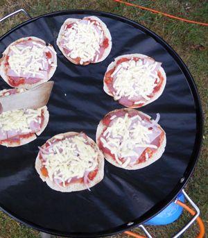 Pizzaatjes op de Skottelbraai. Van een half pita-broodje, met tomatensaus, ham, salami en geraspte kaas. Laten garen met het deksel op de Skottel. Lekker voor de kids.