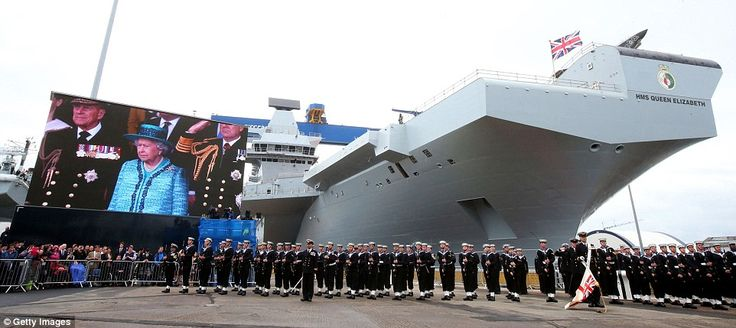 Salute: The Queen is seen watching the ceremony on the big screen situated behind the sailors standing to attention