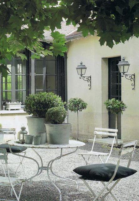 Outdoor dining, metal table & chairs with gravel patio. Boxwoods in metal containes.