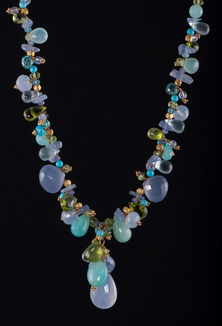 Add a little color to your life with this Laura Gibson 18K yellow gold necklace. The necklace consists of 108 carats of Peruvian opal, tanzanite, peridot, and apatite.