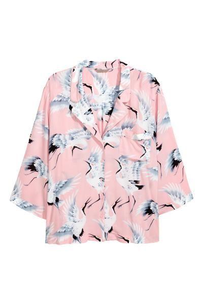 Een wijde blouse van geweven, licht onregelmatige kwaliteit met een geprint dessin. De blouse heeft een kraag, een knoopsluiting voor, een borstzak, verlaag