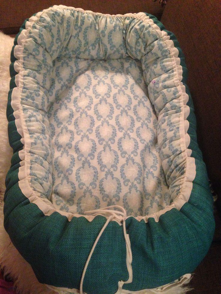 Baby-nest (legg-babyen-der-det-måtte-passe-greie). Møbelstoff som underlag, anorakksnor for å knyte sammen. Superlett!