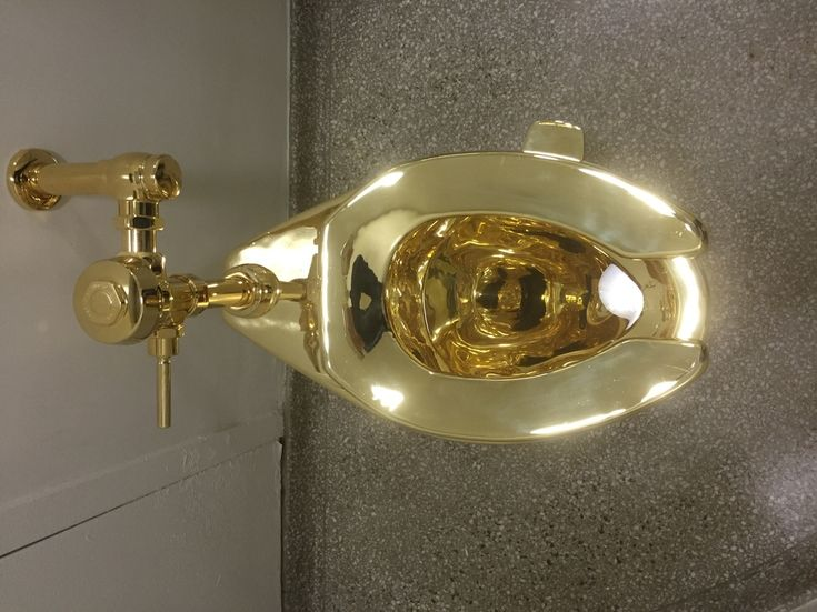 A fully functioning solid gold toilet, made by Italian artist Maurizio Cattelan, is going into public use at the Guggenheim Museum in New York on September 15, 2016. .A guard will be stationed outside the bathroom to protect the work, entitled 'America', which recalls Marcel Duchamp's famous work, 'Fountain'. / AFP / William EDWARDS        (Photo credit should read WILLIAM EDWARDS/AFP/Getty Images)