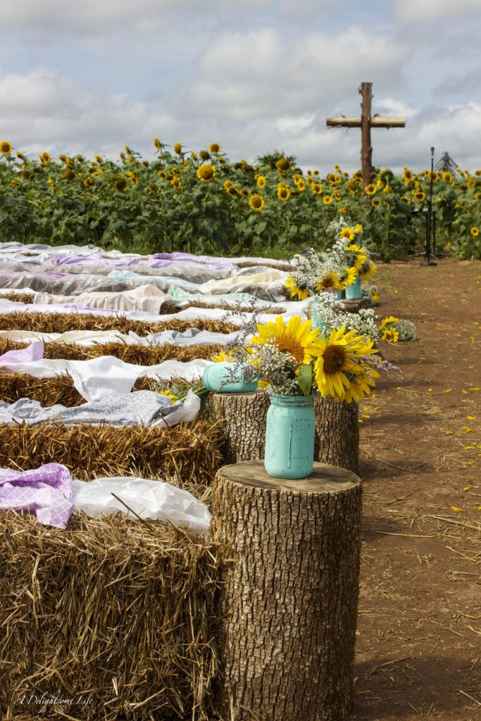 hay bales, painted mason jars and a rugged cross were some of the DIY decor elements my daughter envisioned for her wedding in a sunflower field