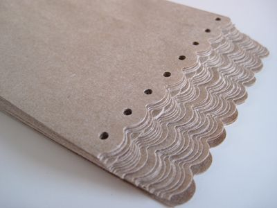 Taking brown paper bags and using punches to trim the tops in a pretty way, great idea found here
