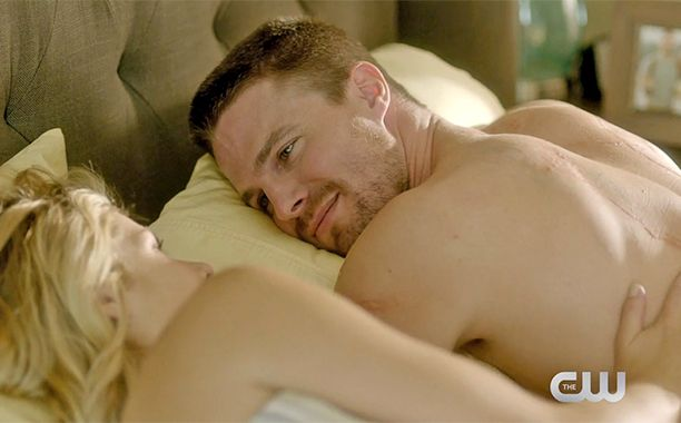 Last we saw them, Oliver and Felicity were riding off into the literal sunset to enjoy a life of vigilante-free happiness. And when Arrow returns, we catch up with the couple five months later. Not only is Felicity now CEO of Palmer Tech, but she's got a hot man to wake up next to.  In a new sneak peek at season 4, we get a glimpse at the happy couple's definition of pillow talk.