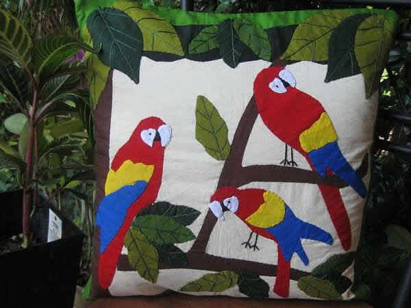 This cotton cushion cover depicts just that- beautiful coloured birds happily content in their natural environment.    The birds and foliage has been hand appliquéd onto a cream coloured cotton base. Hand embroidery defines the leaves. There is a zip at the back of the cushion cover for inserting cushion. The cushion is not included.    Cushion covers is approx. 40 cms by 40 cms.  Handmade and purchased from the fair trade organization, YWCA Craft Centre, Bangladesh.