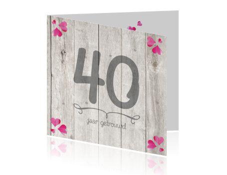 Een moderne 40 jaar getrouwd, robijnen huwelijksjubileum uitnodigingskaart met roze hartjes en houten achtergrond. Trendy kaartje van Luckz.