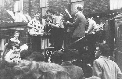 John Lennon performing with the Quarrymen , as Paul checks out the scene (Paul McCartney in the audience looking on, in either glasses or shades.) ... PHOTO: Charles Roberts