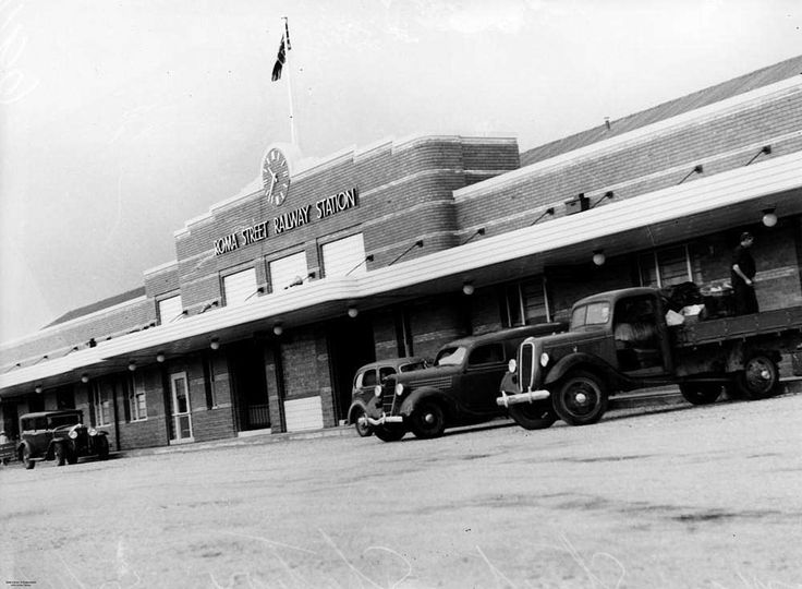 Motor vehicles parked in front of the Roma Street Railway Station, Brisbane, 1940 - Motor vehicles are parked on the street in front of the Roma Street Railway Station. The station clock on the front of the building reads 10:35am