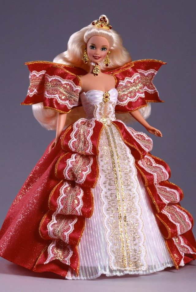 Release Date: 1/1/1997   Barbie® doll is a true image of royal splendor in holiday red, snowy white and glittering gold with a golden tiara adorned with six ruby-colored gemstones. Festive accents include a jeweled choker and earrings.    In 1997, the blond Happy Holidays® Barbie® doll was available exclusively to members of The Official Barbie Collector's ClubSM