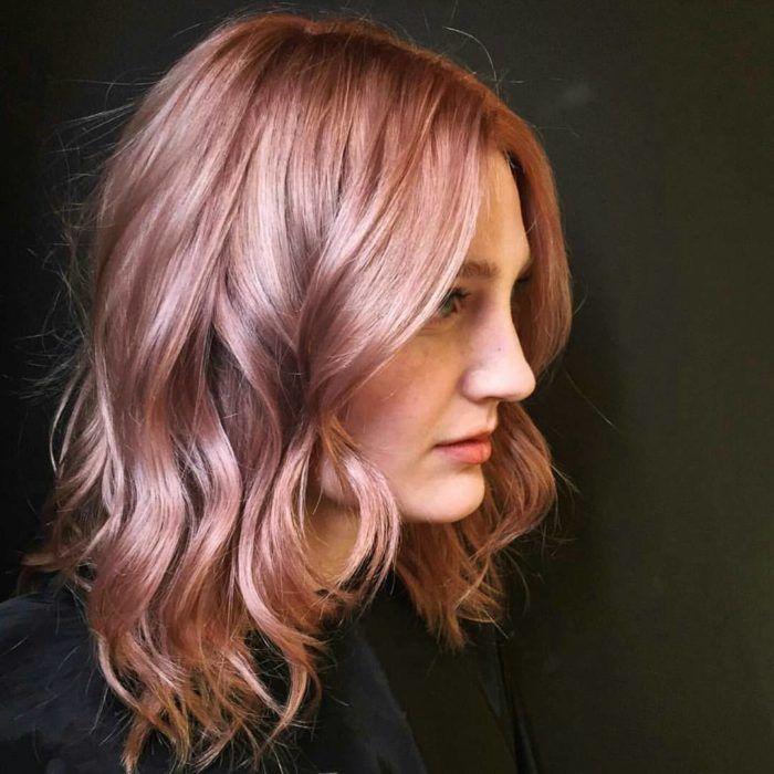 Chica con el cabello rizado pintado en color rosa-dorado con toques de violeta