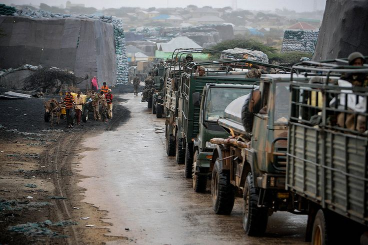 Somali youths pull donkey-drawn water carts past sacks of charcoal as a convoy of the Kenyan Contingent serving with the African Union Mission in Somalia (AMISOM) makes its way through the city of Kismayo.  AU-UN IST PHOTO / STUART PRICE.