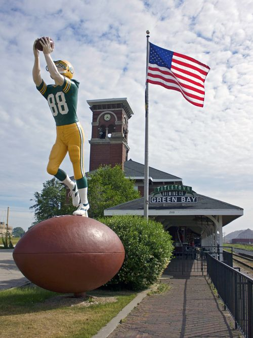 This 22-foot statue has stood in front of the old Packers Hall of Fame for many years until the Hall moved to Lambeau Field, then it had a short stint on the grounds of the Neville Public Museum before winding up in front of the Titletown Brewery.