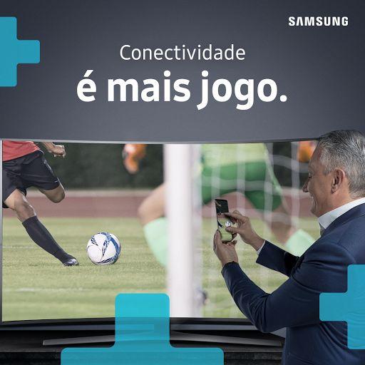"""A versatilidade do Tite ao tomar decisões em campo é como a conexão entre o Samsung Galaxy S8 e a TV 4K Samsung: com apenas alguns toques é possível colocar o que estiver na tela do seu smartphone direto na televisão. Samsung e Tite: uma parceria que é mais jogo.  #PraCegoVer:  Na imagem, o técnico da Seleção Brasileira de Futebol, Tite, fotografa um jogo de futebol na tela de uma TV 4K Samsung com seu Smartphone Galaxy S8. Sobre a imagem, o texto: """"Conectividade é mais jogo."""""""