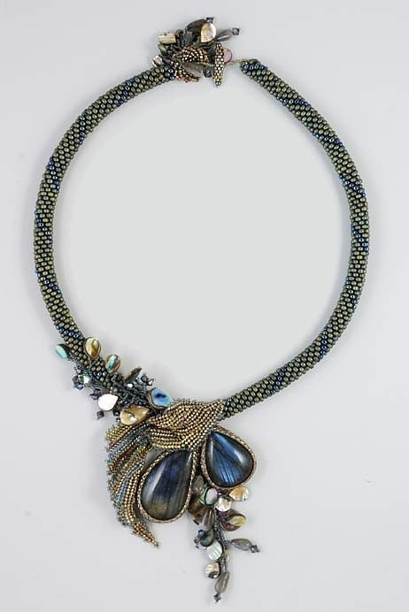 """Replicate.  I think: Necklace chain in either tubular brick stitch or peyote worked flat then zipped up.  Bezels in peyote.  Draping part above cabochons in herringbone.  Toggle in peyote.  Some herringbone decorations at toggle.  Shell elements at toggle and under cabochons added like fringe.  Shell elements above cabochons added like surface embellishments with """"stems."""""""