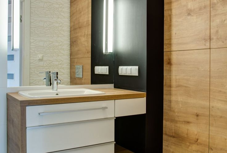 Wnętrze łazienki z drewnianymi elementami w postaci obudowy umywalki i toalety.