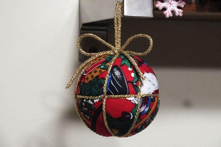 Palla in polistirolo marcata a spicchi ricoperta con quadratini di stoffa natalizia.