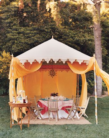 Patio tent ~ Use a popup canopy for a tent! Note how the side curtains are tied to the carpet to keep them from blowing around (well, a few of them are). Keep an eye out for older popup canopies at garage sales. Very quick and easy solution for a tent with lots of room. Keep an eye open for indoor/outdoor carpet on Craigslist or Home Depot sales.