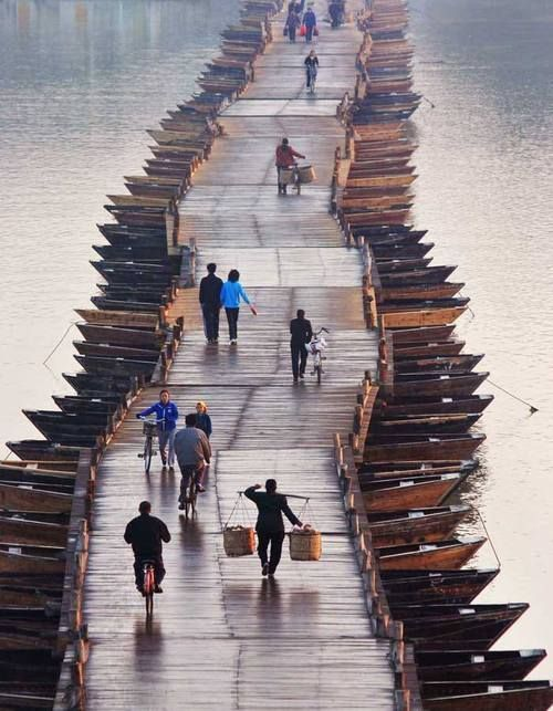 People walk on an ancient floating bridge across the Gongjiang River in Ganzhou, East China's Jiangxi Province, April 1, 2013. The wooden bridge, running 400 meters, is supported by some 100 floating boats anchored in a row. The bridge could date back to the time between 1163 and 1173 during the Song Dynasty, and has become a scene spot of the city. (Xinhua)
