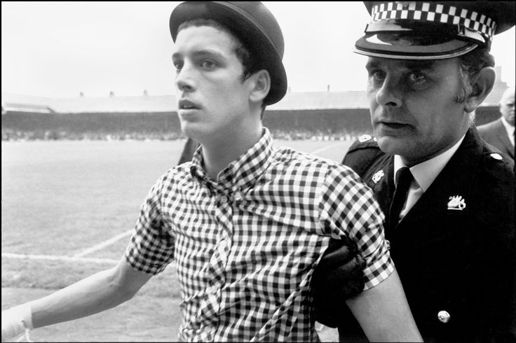 Magnum Photos - Ian Berry G.B. England. Football hooligan being escorted from the pitch after disrupting the match. 1971.