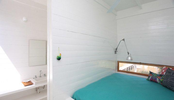 В изголовье кровати в обоих спальнях узкие окна, примерно как на кухне. В качестве ночников использованы лампы на длинной гибкой ножке.  (современный дом,пляжный дом,архитектура,дизайн,экстерьер,интерьер,дизайн интерьера,мебель,спальня,дизайн спальни,интерьер спальни) .