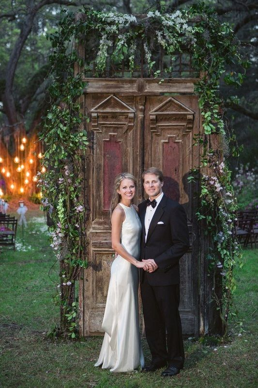 Cameran Eubanks and Dr. Jason Wimberly in front of rustic doors decorated with greenery http://itgirlweddings.com/cameran-eubanks-southern-wedding/