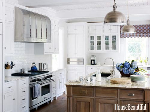 """Italian Marble-Counters and the wire-brushed oak island in the kitchen of a Georgia beach house are topped with Breccia Imperiale, """"the most beautiful milk-white slab of Italian marble you've ever seen,"""" designer Jim Howard says. """"Its aubergine and cool green veining hides everything."""" The scalloped window shade is John Robshaw's Maansi Walnut; barstools are by Halo Styles. Viking range, Waterworks backsplash, RangeCraft hood. Antiqued nickel pendant lights by Visual Comfort."""