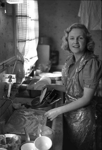 ..c.1940's doing the dishes - What is her apron made of? It looks almost plastic-y, and waterproof?, but it still has frills around the edges. Why don't they make those anymore?! I'm always getting my shirts wet when I wash dishes or clean the counters!