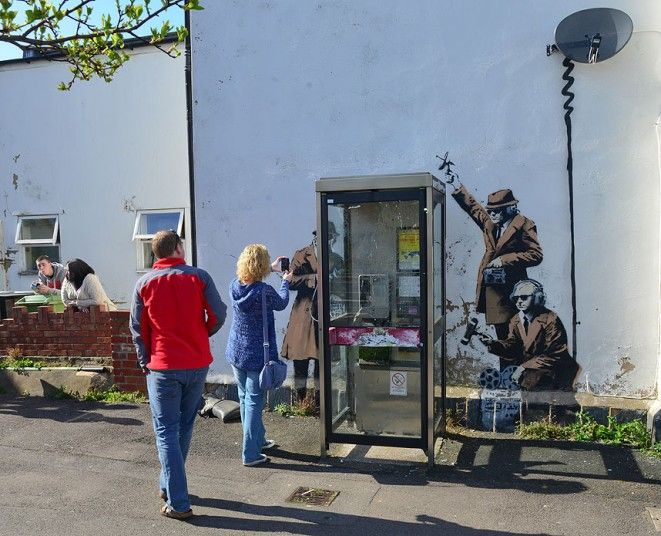 A Banksy art work has appeared on the side of a house depicting government agents 'spying on a phone box' in Cheltenham near the GCHQ (Gover...