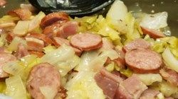 Cabbage cooked in bacon drippings and seasoned with garlic, red pepper flakes and caraway seeds makes a cozy nest for smoked Polish-style sausage in this homey, hearty, and satisfying supper.