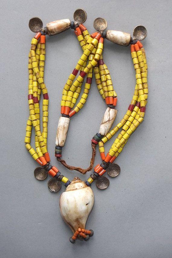 Deze lange zware ketting, strand glas en shell kralen en hangers van kleine messing is afkomstig van de Naga.  De hangende lengte van de ketting is…