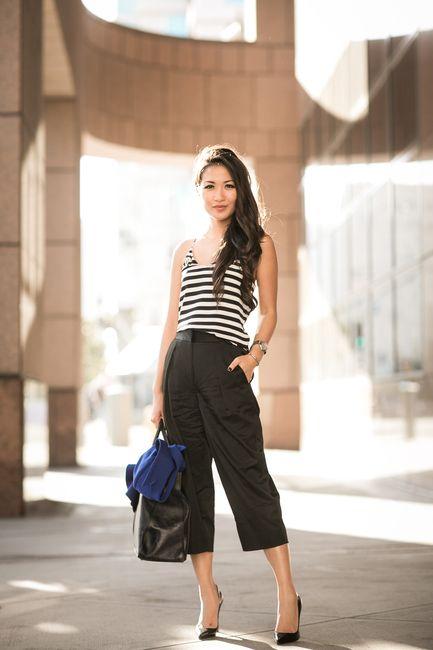 pantacourt escura combinada com blusa listrada e sapato de bico fino e gáspea baixa. Pernas alongadas, cintura marcada e muita elegância.