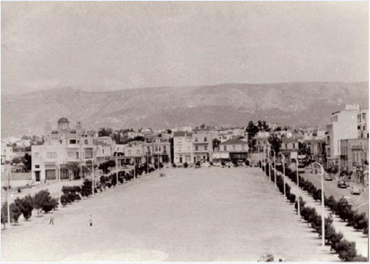 Η κεντρική πλατεία της Νέας Σμύρνης το 1957.  Στο βάθος αριστερά η Αγία Φωτεινή, σύμβολο του προσφυγικού χαρακτήρα της πόλης