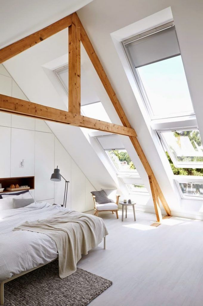 Scandinavian designed attic master bedroom with wood beams, light wood floor, sloped wall with skylight windows and built-in storage.