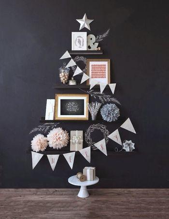 壁にある飾り棚を利用して、そこに雑貨や写真立てをツリーのシルエットに並べるだけ!黒の壁にやわらかい色の雑貨たちが映える、シックなツリーです。