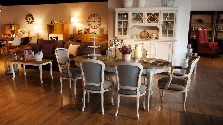 Elegancki zestaw mebli do jadalni. Duży stół o zaokrąglonych bokach, szarym blacie i białych nogach. Krzesła z tapicerowanym siedziskiem i oparciem w kolorze szarym, z drewnianymi nogami w kolorze białym.