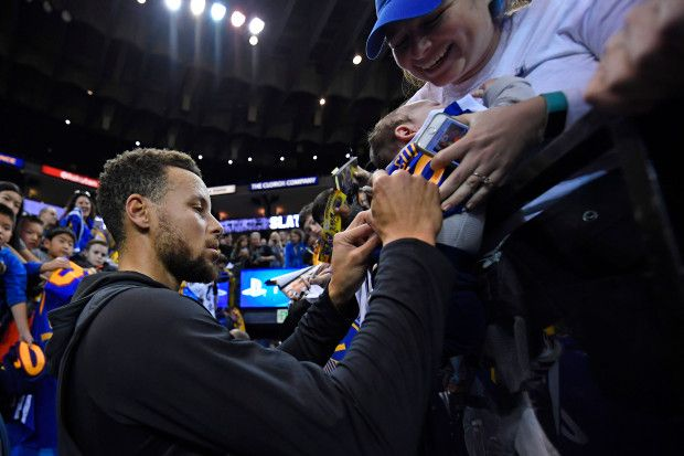 A woman lowers her baby to have Golden State Warriors' Stephen Curry (30) autograph his jersey before the start of their NBA game at the Oracle Arena in Oakland, Calif., on Saturday, Dec. 30, 2017. Curry returns to the floor tonight after sustaining an ankle injury on Dec. 4th. (Jose Carlos Fajardo/Bay Area News Group)
